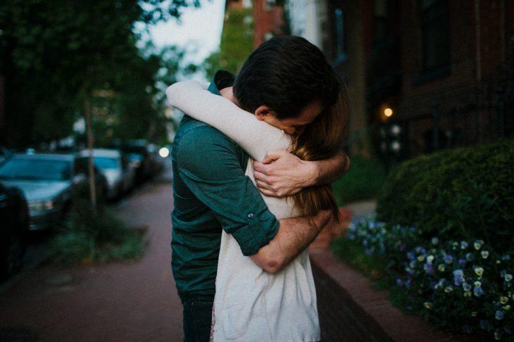 Pareja abrazada fuertemente en la calle