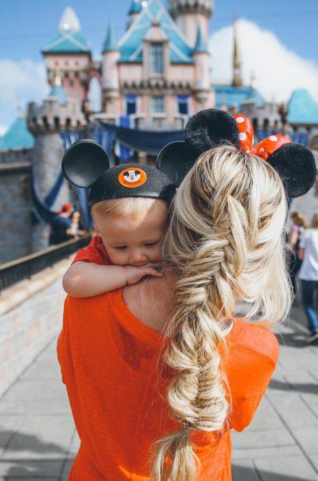Chica cargando un bebé con orejas de mickey en Disney