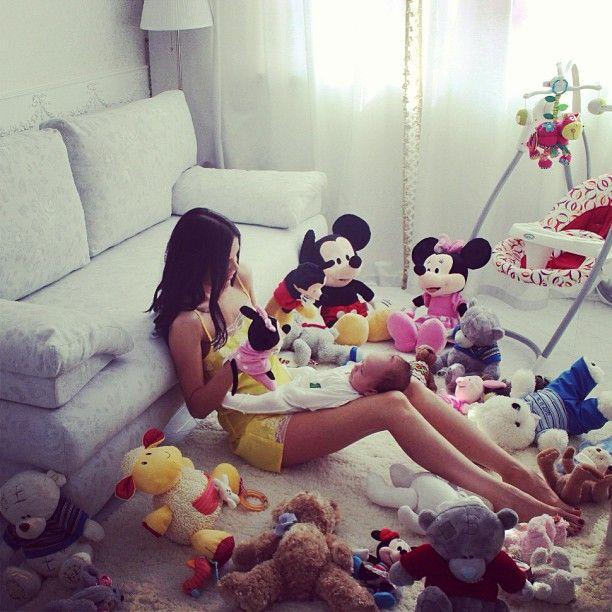Chica rodeada de peluches jugando con un bebé