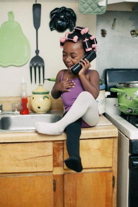 Niña de color hablando por teléfono felizmente