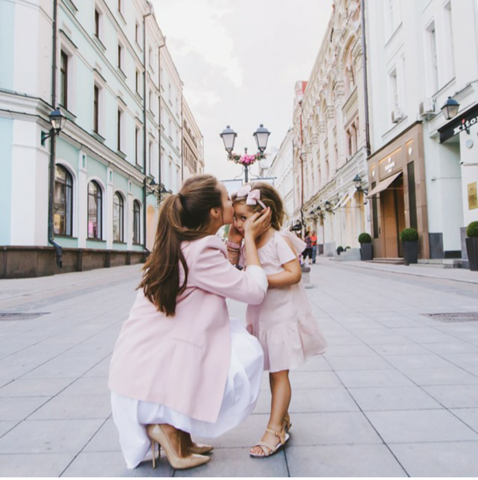 Chica besando la frente de una pequeña niña