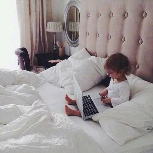 Niño pequeño con una computadora en una cama