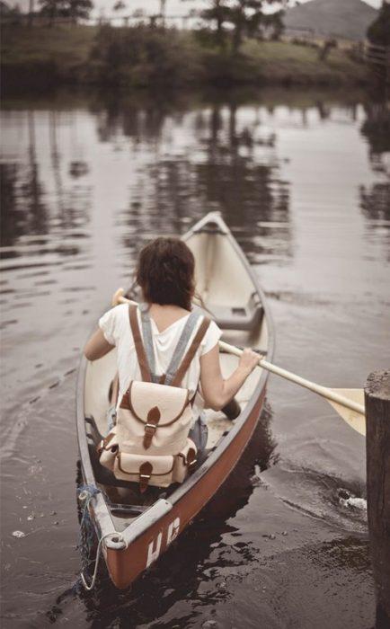 Chica remando un bote en un lago