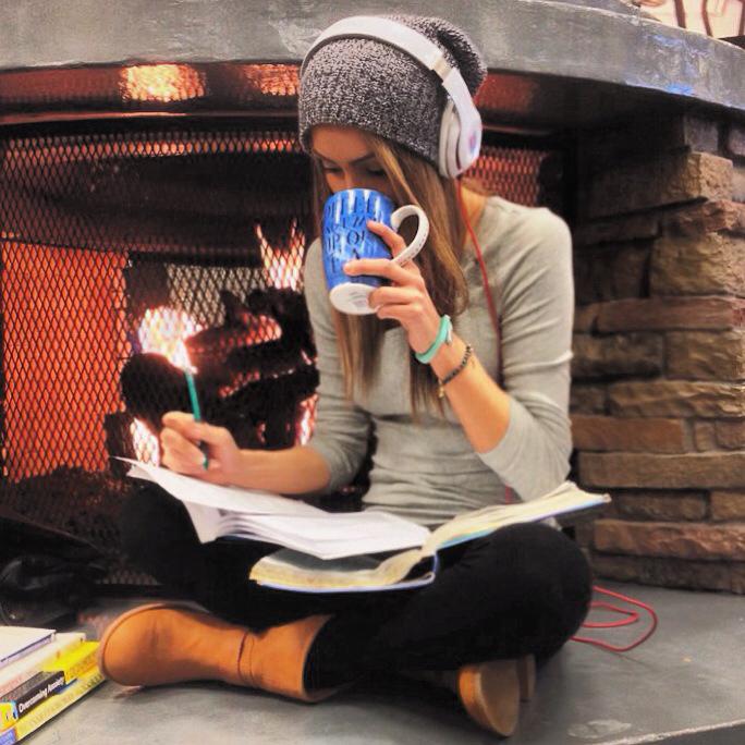 Chica estudiando, tomando café y escuchando música