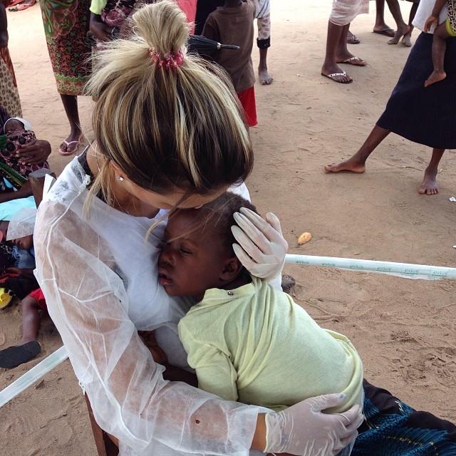 Chica voluntaria abrazando a un niño en África