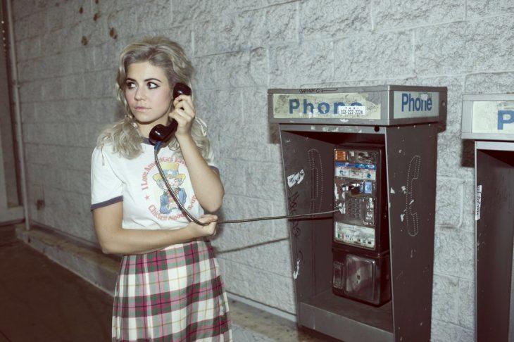 Chica noventera hablando desde un teléfono público