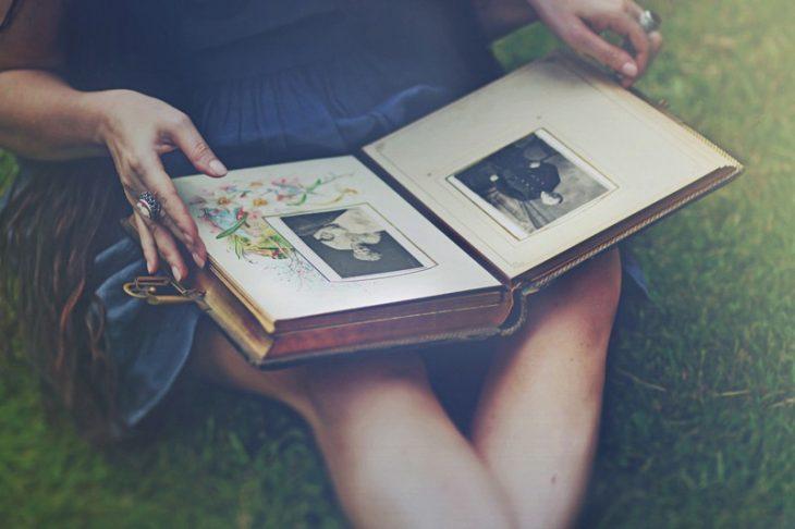 Chica viendo un álbum fotográfico vintage