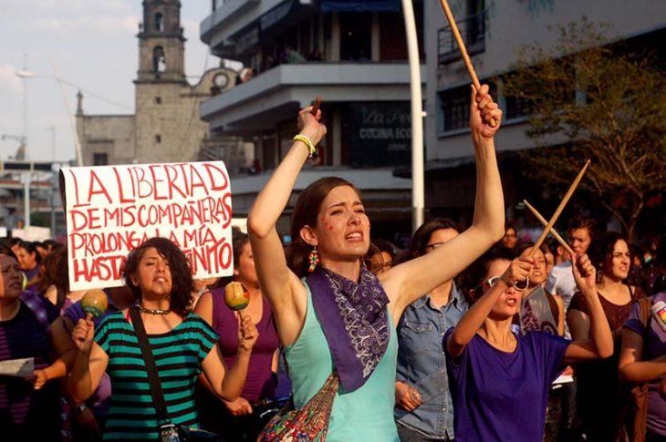 mujeres feministas en marcha en contra de violencia pancartas y palos