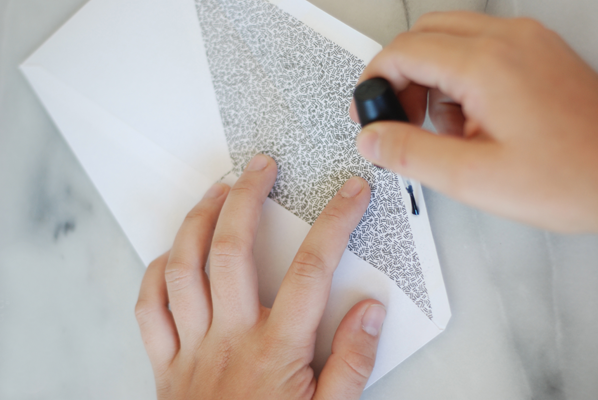 sobre y manos con esmalte de uñas transparente