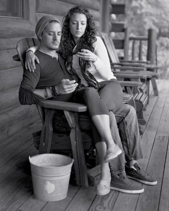 hombre sentado en una silla y mujer en sus piernas miran sus manos