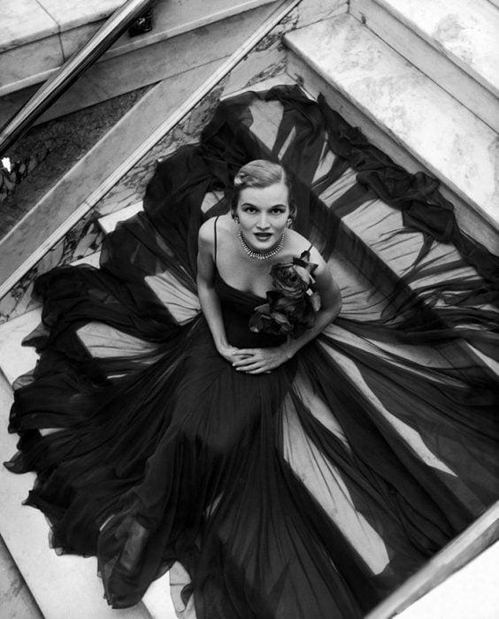 Fotografía de Nina Leen donde aparece una mujer de los años 50 0 60 sentada en una escalera con un vestido de gala