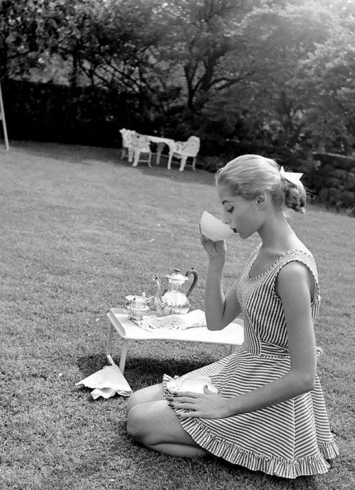 Fotografía de Nina Leen donde aparece una mujer de los años 50 0 60 tomando té en un jardín