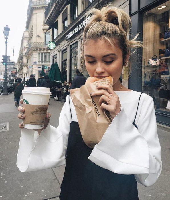 Chica comiendo un pan y café de starbucks