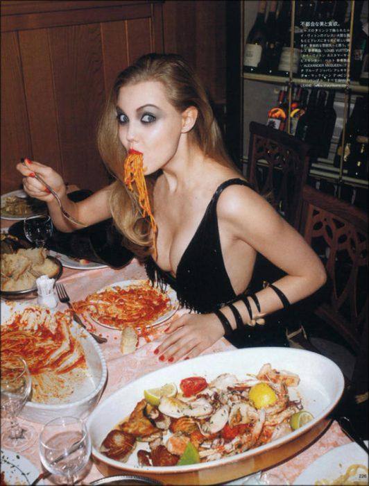 Chica sentada comiendo spaguetis