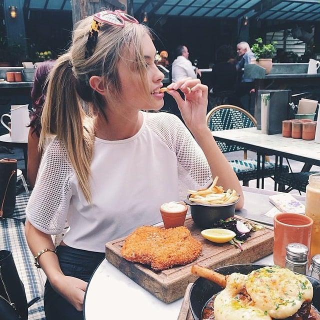 Chica comiendo una hamburguesa con papas fritas