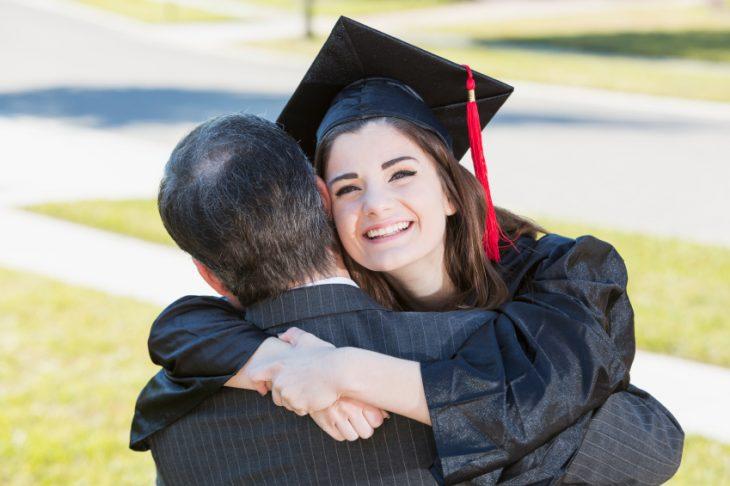 chica con toga y birrete abrazando a su padre
