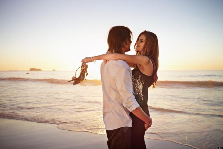 Pareja de jóvenes abrazándose en la playa.