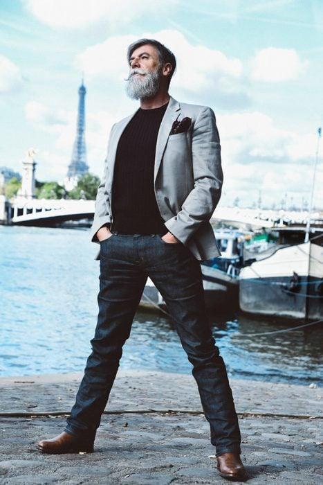 Hombre de 60 años que es modelo posando al lado de un puerto con yates