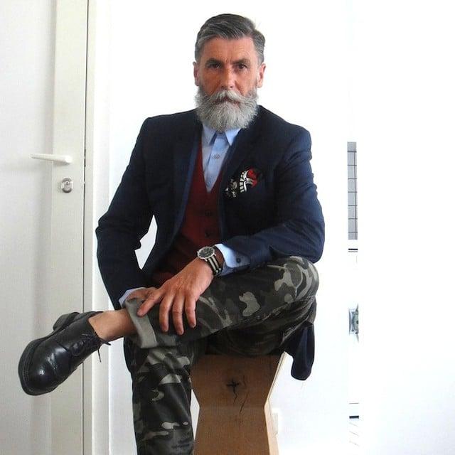 Hombre de 60 años que es modelo sentado en un banco posando para una sesión de fotos