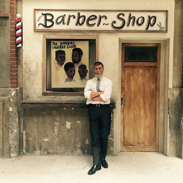 Hombre de 60 años que es modelo posado para una sesión de fotos mientras está recargado en la pared de una barbería