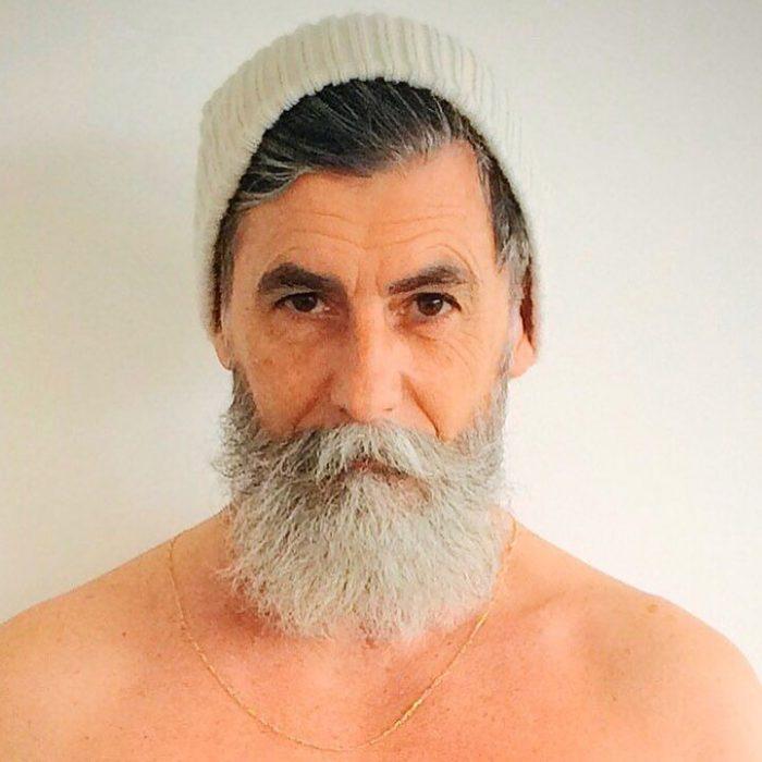 Hombre de 60 años que es modelo posando para una sesión de fotos mientra usa una boina
