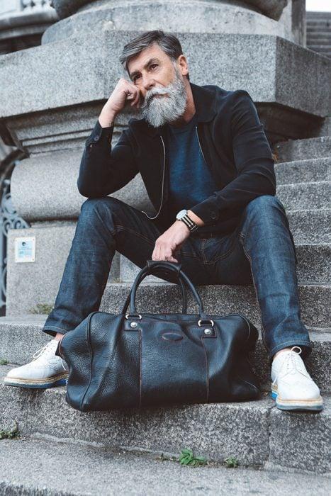 Hombre de 60 años que es modelo posando para una sesión de fotos que incluye una bolsa mientras estpa sentado en unas escaleras