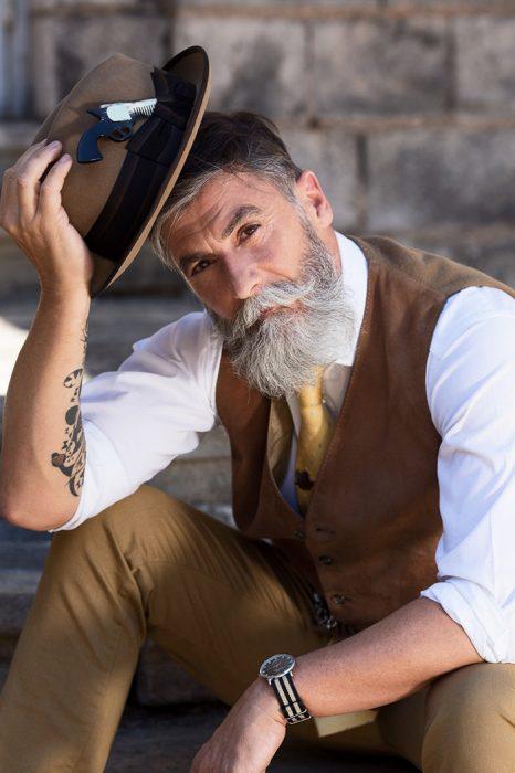 Hombre de 60 años que es modelo posand con un sombrero