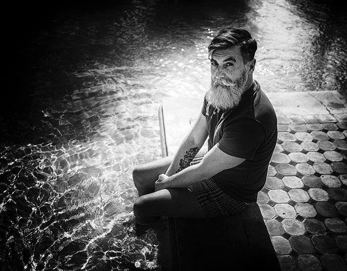 Hombre de 60 años que es modelo sentado a la orilla de un muelle