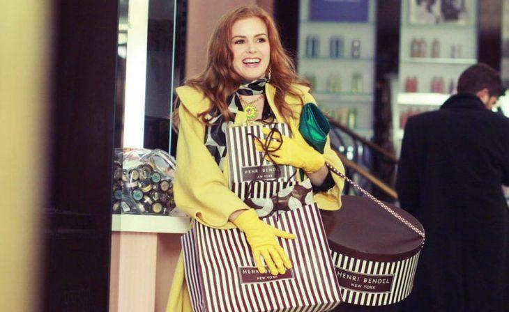 mujer rubia con ropa amarilla y bolsas de compras