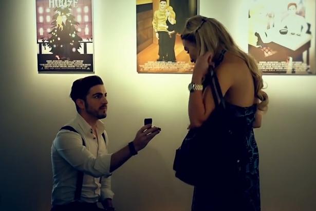 Jason proponiendo matrimonio a su novia Simmone en una galería de arte