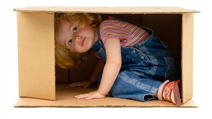 niña pequeña se esconde en caja