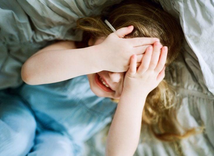 niña se tapa la cara con manos