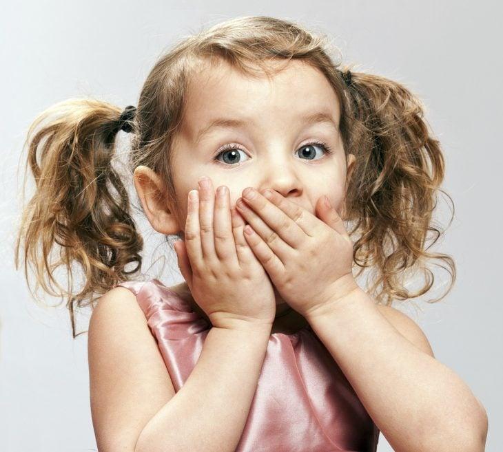 niña tapándose la boca