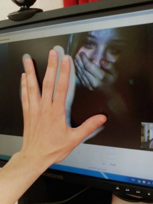 mujer llorando en videollamada y manos en la pantalla