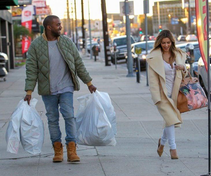mujer caminando en la calle y hombre con bolsas de compras