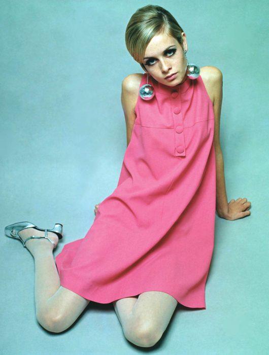 Supermodelo Twiggy usando un vestido simétrico de color rosa