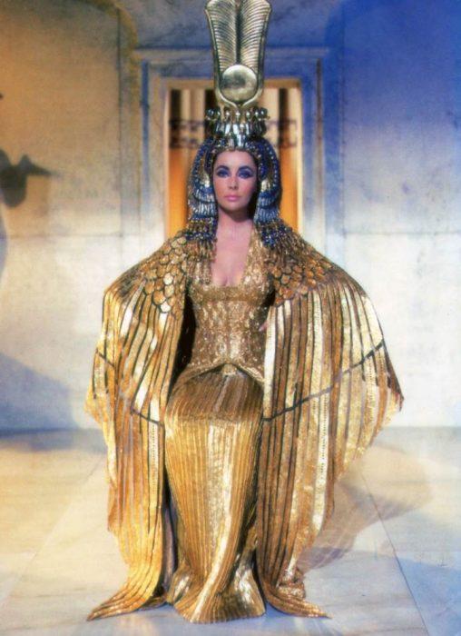 Elizabeth Taylor usando un vestido en color dorado durante la película de Cleopatra en 1963