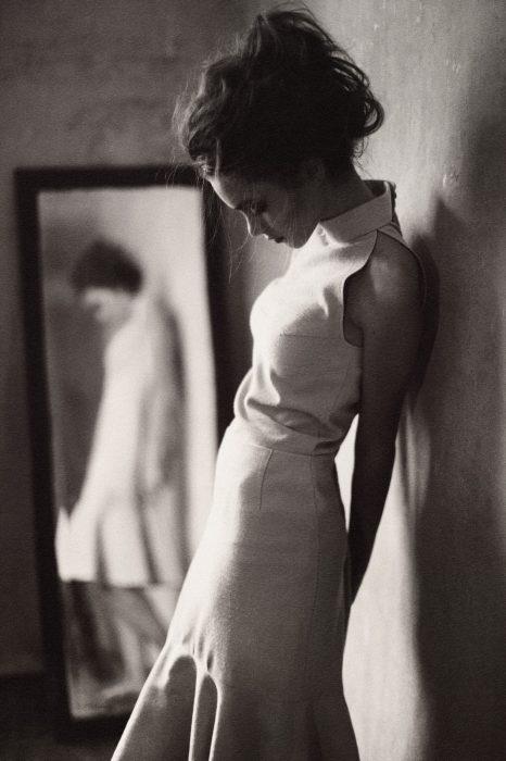 mujer con vestido blanco y espejo atras