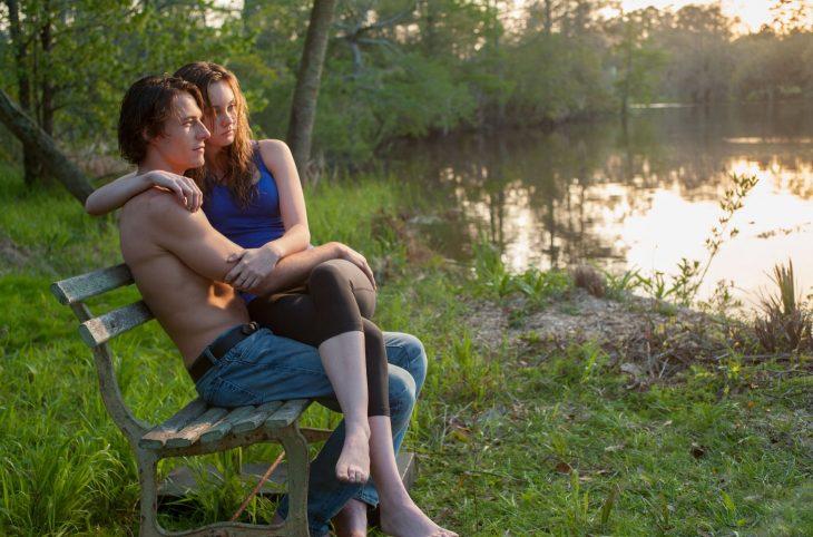 hombre sentado en banca y mujer en sus brazos