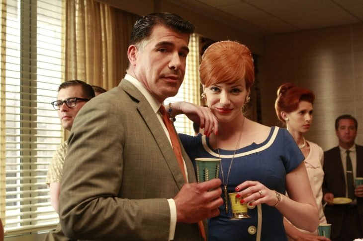 hombre de saco y corbata con bebida en la mano y mujer rubia de vestido azul mirando al frente