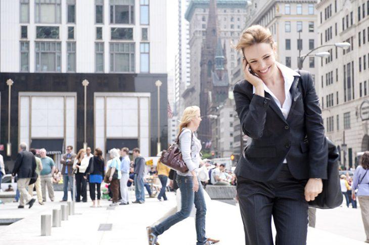 mujer sonriendo hablando por teléfono en la calle