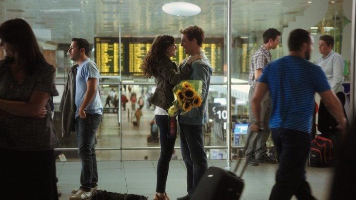 pareja en aeropuerto con ramo de flores en las manos