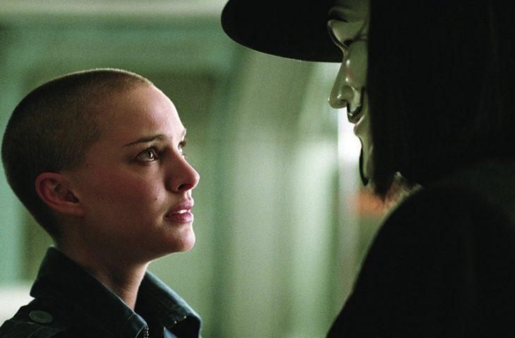 mujer rapada viendo a hombre de mascara con sombrero y cabello largo