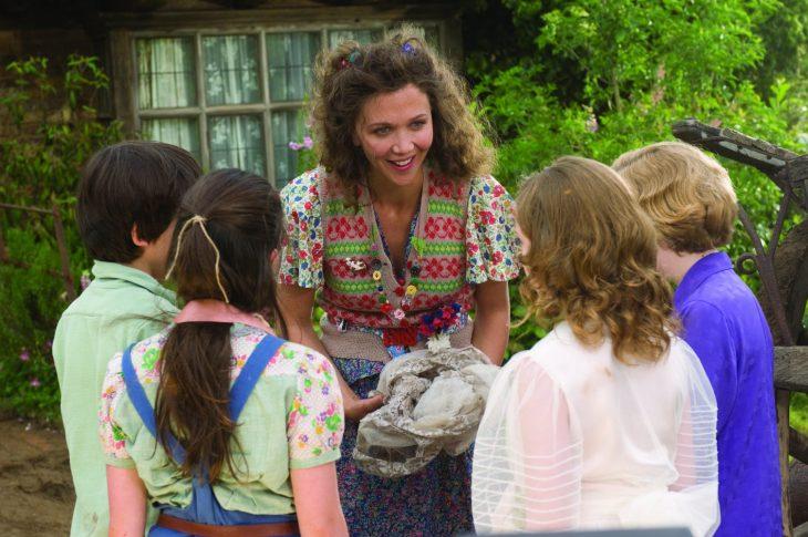 mujer de cabello negro frente a niños y niñas enseñando algo