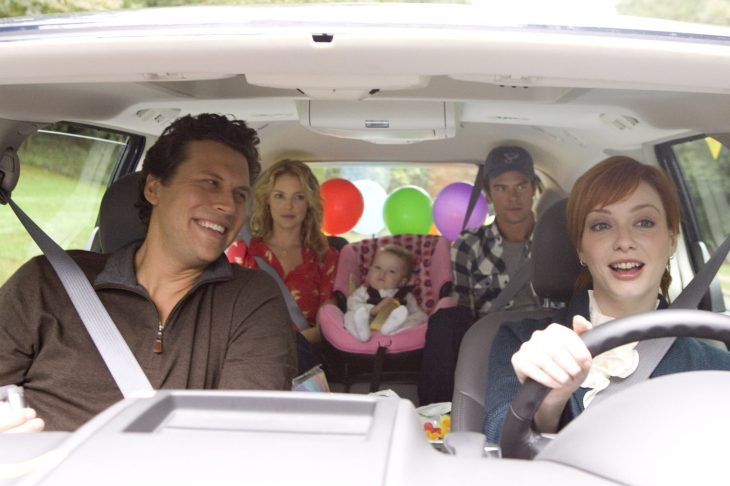 familia en el coche hombre de cabello negro y mujer pelirroja manejando