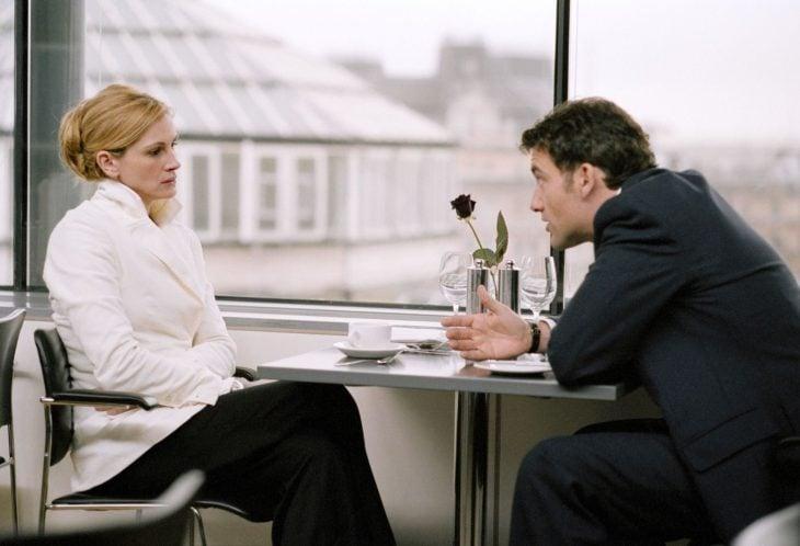 mujer rubia sentada frente a hombre discutiendo