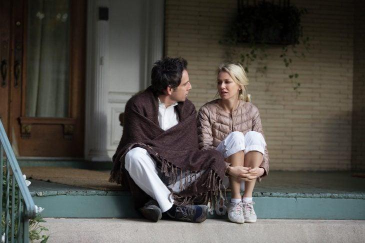 hombre y mujer sentados en escaleras con pijama platicando