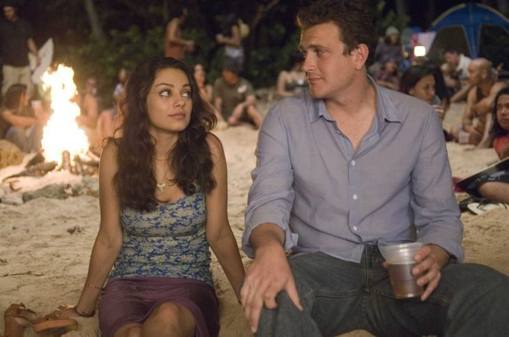 mujer pensando y hombre a un lado sentados en la playa