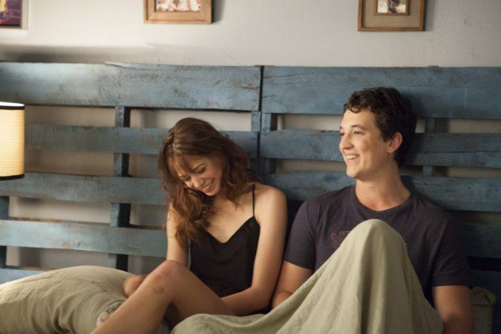 pareja sentada en la cama riéndose