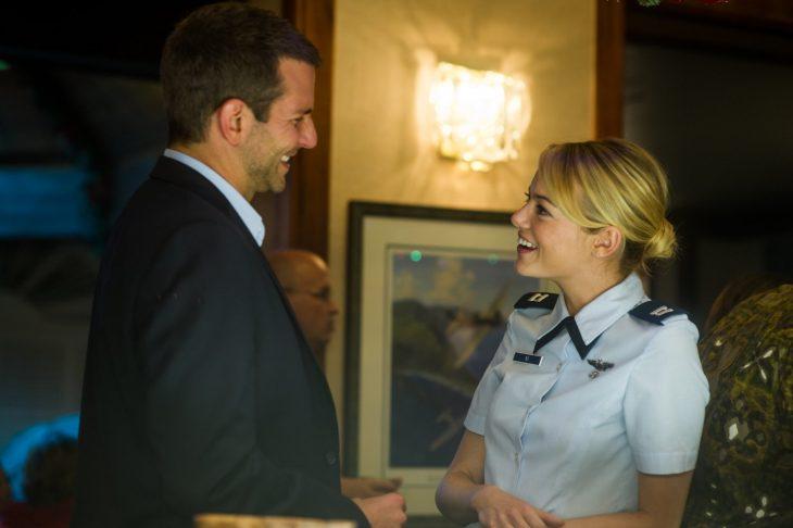 hombre con saco y mujer con uniforme sonriendo